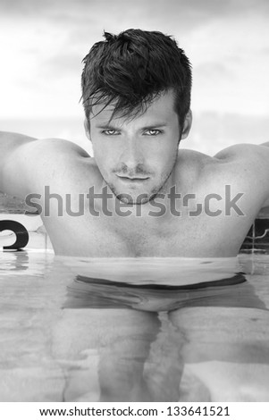Fashion portrait of a gorgeous male model relaxing in luxurious swimming pool