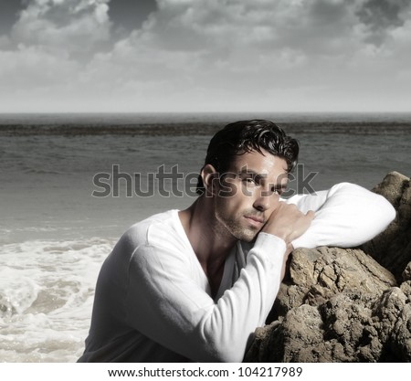 Fashion portrait of a handsome man in exotic  beautiful beach landscape - stock photo