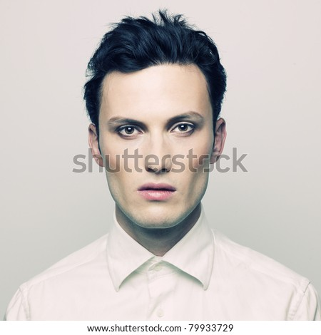 Fashion portrait of a handsome young man with make-up - stock photo