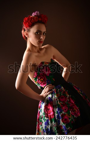 Fashion portrait of a redhead woman with flowers in hair, sitting on wooden chair. Attractive redhead woman. Studio shot