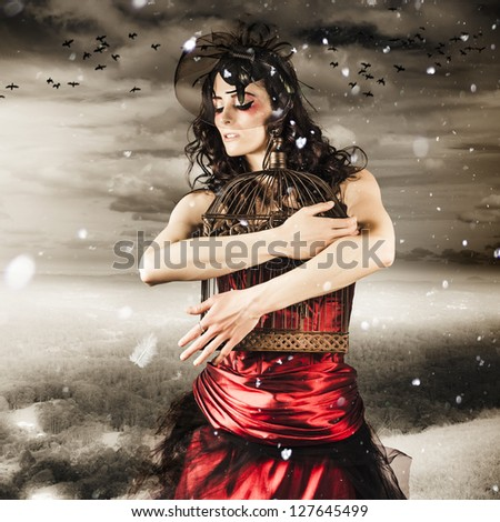 Fashion Portrait Of A Romantic Woman Feeling The Cold Grasp Of Winter When Releasing Her Love To Freedom From A Snow Capped Romance - stock photo