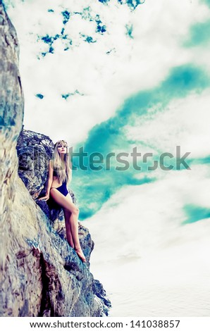 fashion portrait of a sensual blonde on a  stones