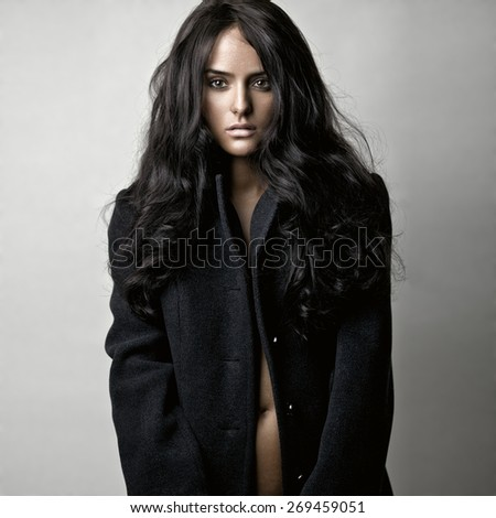 Fashion portrait of a sensual brunette girl in black coat with curly long black hair. - stock photo