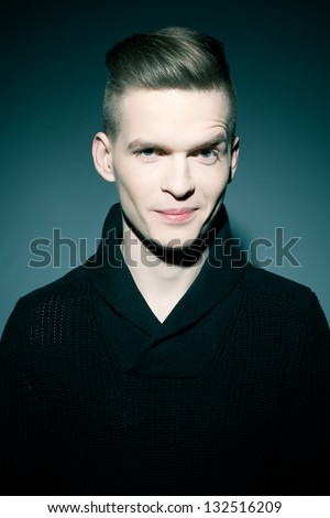 Fashion portrait of a smiling elegant young and handsome man posing over dark blue background. Studio shot - stock photo