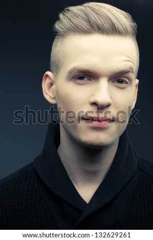 Fashion portrait of a smiling elegant young and handsome man with blond hair and great stylish haircut posing over dark blue background. Hipster style. Close up. Studio shot - stock photo