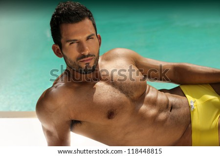 Fashion portrait of a very muscular sexy man relaxing at swimming pool - stock photo