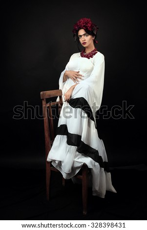 Fashion portrait of a woman with flowers in hair, standing near the wooden chair. Fashion portrait of a brunette woman posing as Frida Kahlo. Close up portrait. Studio shot - stock photo