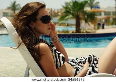 fashion portrait of a young beautiful woman wearing sunglasses - stock photo