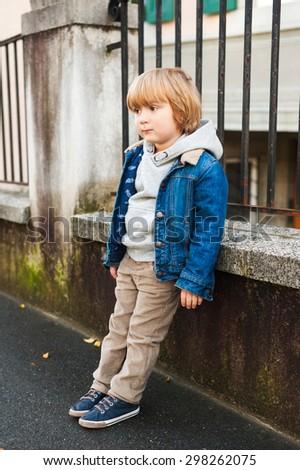 Fashion portrait of adorable little boy wearing denim jacket, beige corduroy trousers, gray sweatshirt and blue shoes - stock photo