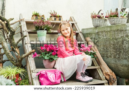 Fashion portrait of adorable little girl on a street in a city - stock photo