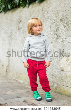 Fashion portrait of adorable toddler boy wearing grey sweatshirt, red trainings and green shoes - stock photo