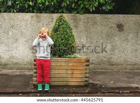 Fashion portrait of adorable toddler boy wearing grey sweatshirt, red trainings and green shoes. Kid pretending taking pictures with his hands - stock photo