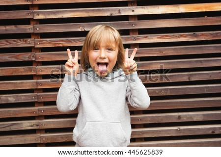 Fashion portrait of adorable toddler boy wearing grey sweatshirt, standing against wooden background - stock photo
