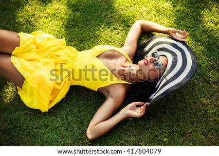 Fashion portrait of amazing girls, lady lying on green grass in a bright yellow dress in a luxurious wide striped hat, retro sunglasses, sensual glamour, makeup with red lips clean healthy skin face   - stock photo