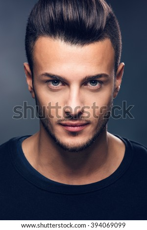 Fashion portrait of an attractive young man in the studio, close up. Beauty concept. Toned photo. - stock photo
