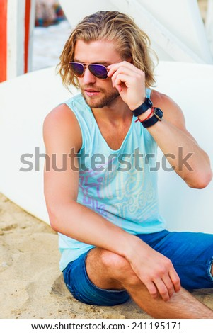 Fashion portrait of an attractive young  sexy man with perfect long light hair  on a tropical beach .  He sitting on a background of a surfboard. Warm summer colors. - stock photo