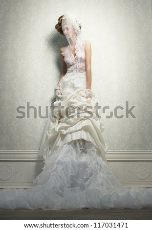 Fashion portrait of an elegant bride leaning against a wall - stock photo