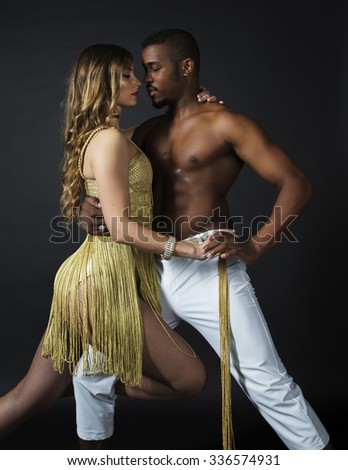 Fashion portrait of attractive dancing couple. Sensual looking each other. Hugging, holding hands. Dancing latino. Passion, love. Sensuality. Girl's perfect skin facial make-up. The guy's pumped abs - stock photo