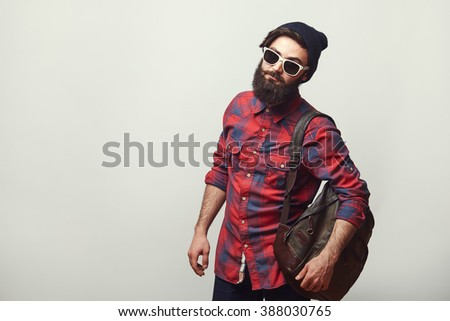 Fashion portrait of bearded hipster young man wearing sunglasses, backpack and hat over grey background with copyspace. Confident man with beard. - stock photo