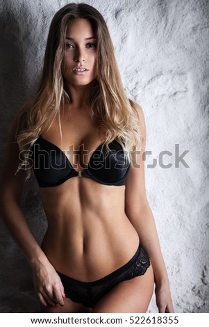 Fashion portrait of beautiful female model posing in black lingerie near white wall