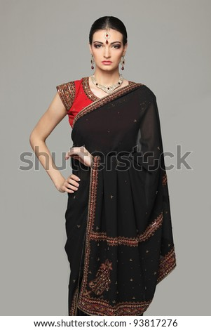 Fashion portrait of beautiful female wearing traditional indian costume, over grey background - stock photo