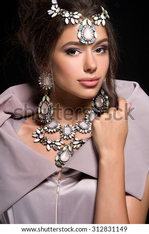 Fashion portrait of beautiful girl with dark hair in luxurious sequin dress