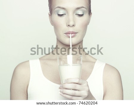 Fashion portrait of beautiful girl with glass of milk - stock photo