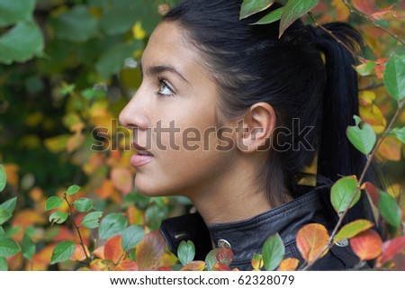 Fashion Portrait of Beautiful girl with leaves close-up. More images of this models you can find in my portfolio - stock photo