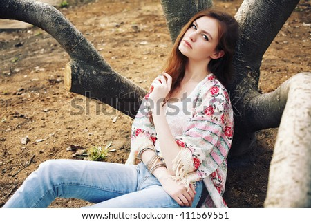 Fashion portrait of beautiful hippie young woman wearing boho chic clothes. Soft warm vintage color tone. Artsy bohemian style. Outdoors, tribal glam, suede ankle boots, kimono