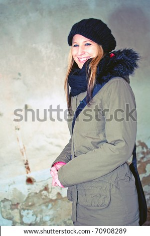 fashion portrait of beautiful smiling young woman posing by the wall of abandoned building - stock photo