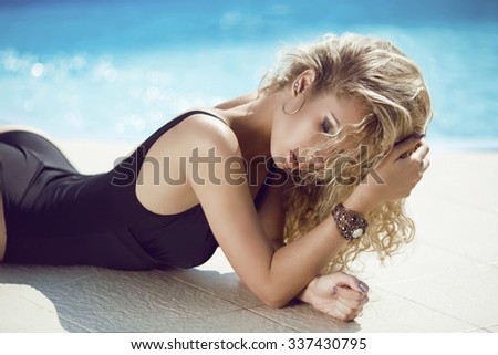 fashion portrait of beautiful tanned woman with blond hair in elegant black bikini relaxing beside blue swimming pool - stock photo