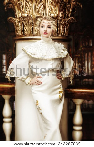 Fashion portrait of beautiful woman in long white dress in an old palace interior. Vintage style. Baroque. Toned photo and noise added. - stock photo