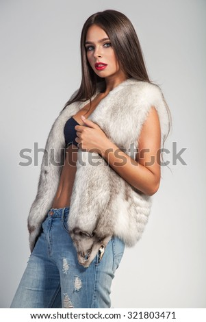 Fashion portrait of beautiful woman in trendy jeans and fur mink vest over grey background. - stock photo