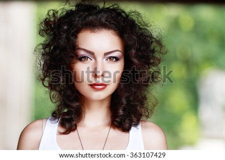 Fashion portrait of beautiful woman with red curly hair and natural makeup enjoying her life in nature. Outdoor shot. Copyspace.
