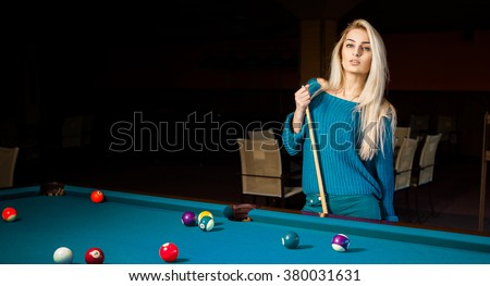 Fashion portrait of beautiful young blonde girl plays billiard. Billiard sport concept. Pool billiard game. American pool billiard. - stock photo