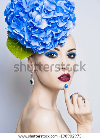 Fashion portrait of beautiful young lady with blue hydrangea - stock photo