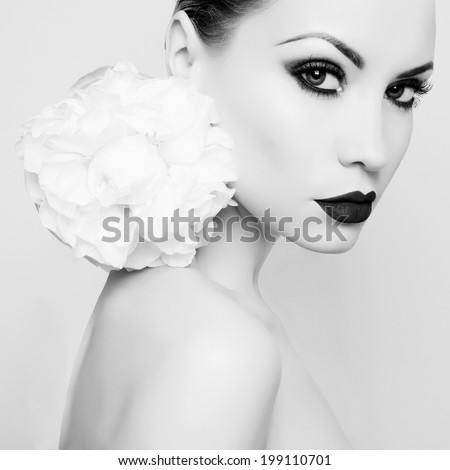Fashion portrait of beautiful young lady with peony - stock photo