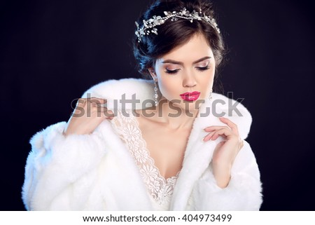 Fashion portrait of beautiful young woman in white fur coat with expensive jewelry, makeup and wedding hairstyle isolated on black background. - stock photo