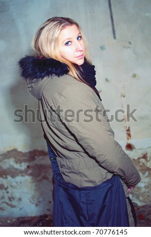 fashion portrait of beautiful young woman posing by the wall of abandoned building - stock photo