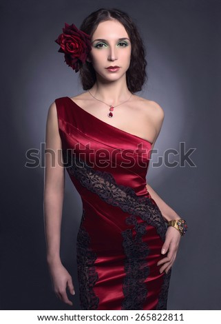 fashion portrait of Beautiful young woman wearing red rose dress.Spanish girl.Flower in hair - stock photo