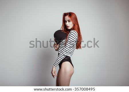 Fashion portrait of beautiful young woman with redhead. Girl in black bodysuit and sweatshirt with black hat on white background. Studio photo. Ideal figure. - stock photo