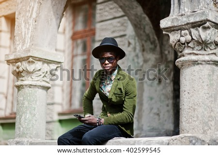 Fashion portrait of black african american man on green velvet jacket and black hat, sitting on the railing and look at camera, holding his smartphone at hand background old vintage house with arch  - stock photo