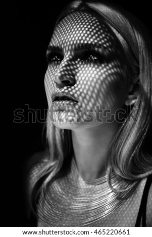 Fashion portrait of  blonde woman with jewelry and bright makeup. Mesh shadow. Black and white