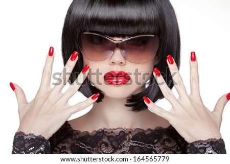 Fashion portrait of brunette woman in sunglasses showing red manicured polish nails. Professional makeup and hairstyle. Model isolated on white background. - stock photo