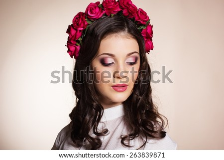 Fashion portrait of cute teenager girl with nice makeup is wearing white blouse and red roses wreath on her head - stock photo