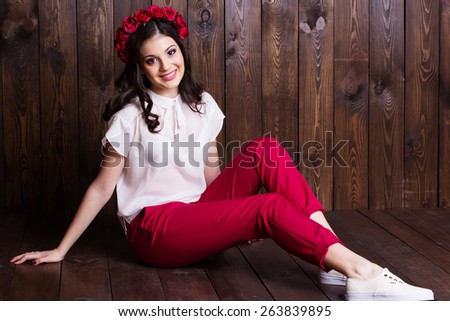 Fashion portrait of cute teenager girl with nice makeup is wearing white blouse and red roses wreath on her head sitting on wooden background  - stock photo