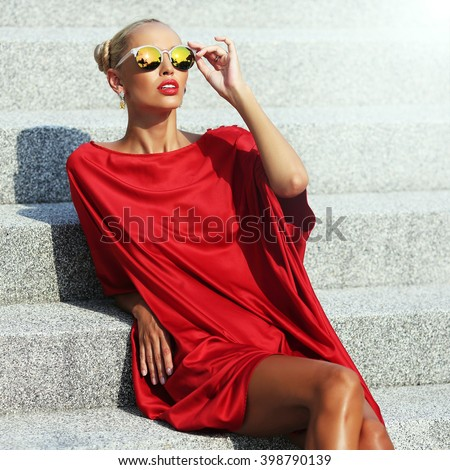 Fashion portrait of elegant stylish girl in a red dress and sunglasses - stock photo