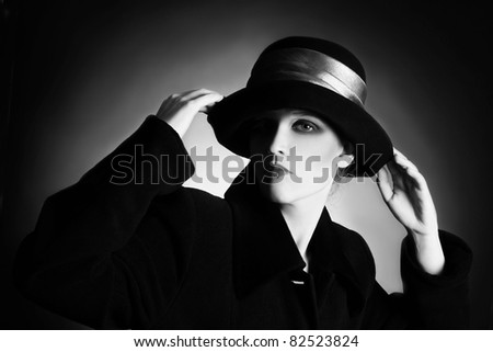 Fashion portrait of elegant woman in black and white hat and coat - stock photo