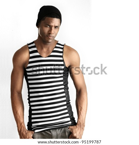 Fashion portrait of fit young male model in black and white striped trendy sleeveless shirt against white neutral background with copy space - stock photo