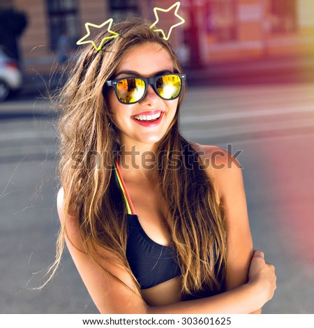 Fashion portrait of funny pretty teen woman, posing on the street, Instagram toned colors. wearing crop top and mirrored sunglasses. - stock photo